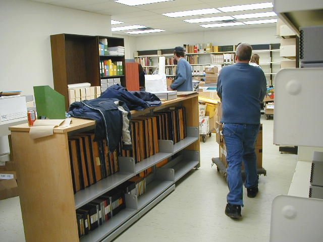 Office with many shelves containing albums, books and archival boxes. People moving boxes on carts.