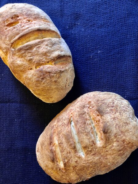 Two loaves of bread on a navy tablecloth