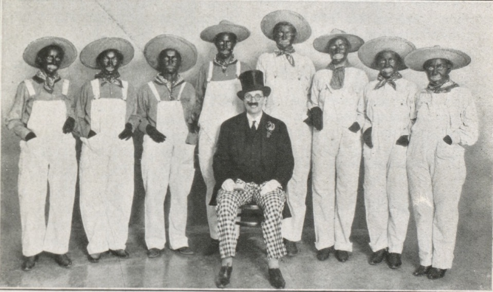 A group portrait of an all female, white minstrel show cast, 8 of whom are in blackface, one who is dressed in top hat and tails.