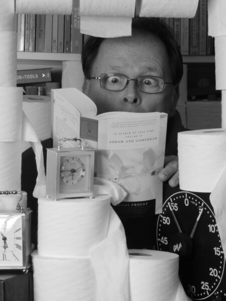 Black and white self portrait of a man reading a book surrounded by toilet paper rolls